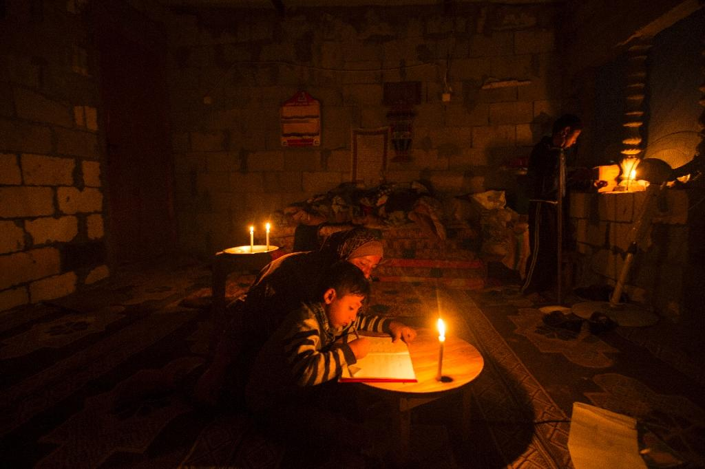 A Palestinian woman helps her son study, by candlelight, at their makeshift home in the Khan Yunis refugee camp in the southern Gaza Strip on April 19, 2017 (AFP Photo/MAHMUD HAMS)