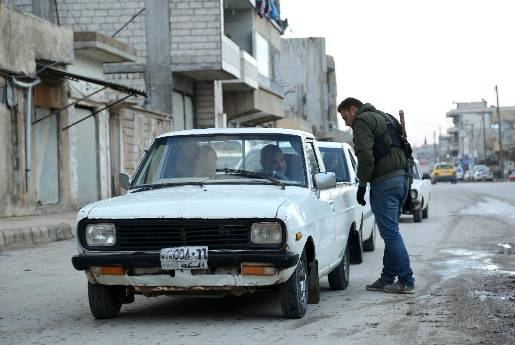 Kurdish militia check vehicles in the city of Qamishli, which is under shared control of the Syrian regime and Kurdish authorities