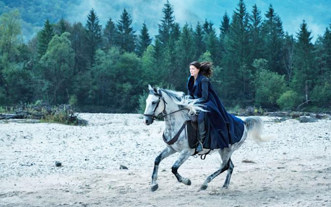 A still from Amazon's 'Wheel of Time' TV series, showing Rosamund Pike riding on a horse over sand and gravel with trees in the background.