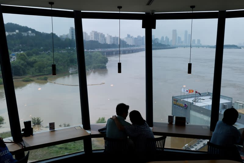 A couple looks at a flooded Han River park in Seoul
