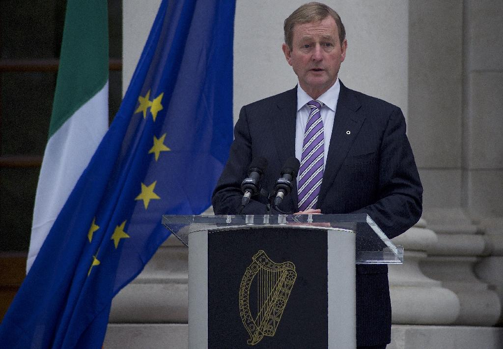 Ireland's Prime Minister Enda Kenny stands alongside the Irish national flag, and the EU flag, as he speaks during a joint press conference with European Council President Donald Tusk outside government buildings in Dublin on September 7, 2016 (AFP Photo/Paulo Nunes dos Santos)