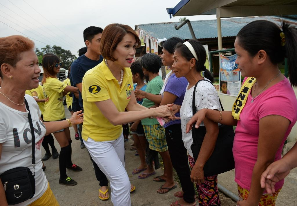 Legislator candidate Geraldine Roman (in yellow) shakes hands with voters during a campaign trip to the town of Orani, Bataan province, north of Manila (AFP Photo/Ted Aljibe)