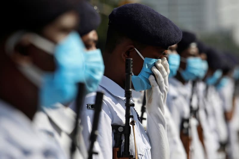 A member of Kolkata police adjusts his face mask as he takes part in rehearsal for the Independence Day parade, after authorities eased lockdown restrictions that were imposed to slow the spread of the coronavirus disease, in Kolkata