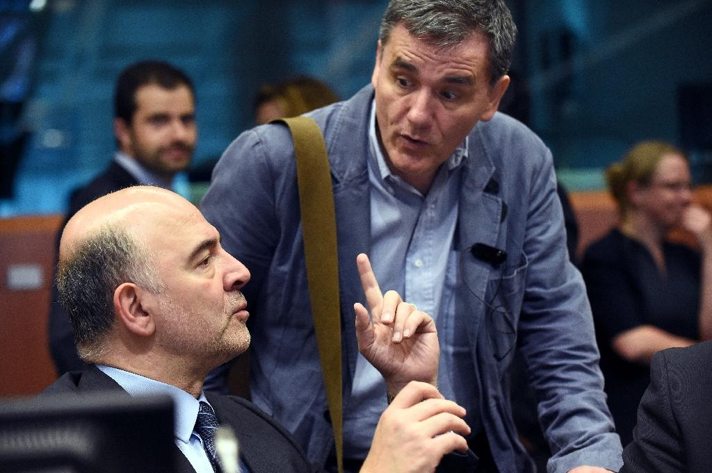 European Union Commissioner of Economic, Financial Affairs, Taxation and Customs Pierre Moscovici (L) talks with Greek Finance Minister Euclid Tsakalotos (R) during a Eurogroup meeting on May 24, 2016 (AFP Photo/John Thys)