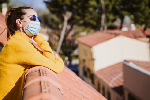 young woman at home on a terrace wearing protective mask and enjoying a sunny day. Corona virus Covid-19 concept