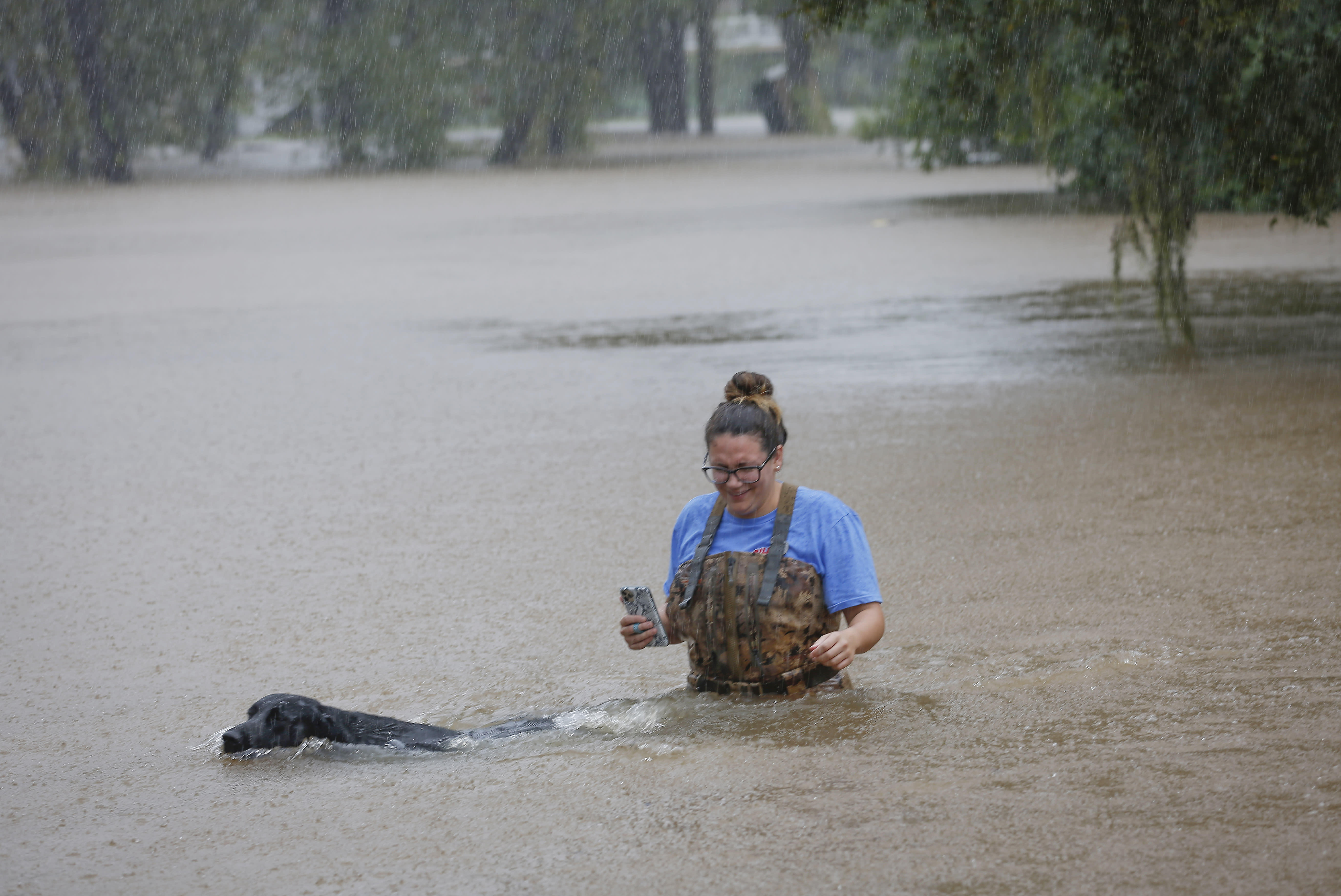 """Adelle Puma and her dog """"Ridge"""" makes their way from the submerged Mary Xing bridge over Marys Creek that leads into Clear Creek as Tropical Storm Beta rainfall trained over the area Tuesday, Sept. 22, 2020, in Friendswood, Texas. Puma and her husband just moved from Breaex Bridge, La., a moth ago and their home sits next to the bridge. (Steve Gonzales/Houston Chronicle via AP)"""