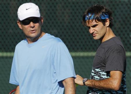 Roger Federer walks on a practice court with coach Paul Annacone during a workout while preparing for the Indian Wells ATP tennis tournament in Indian Wells, California,