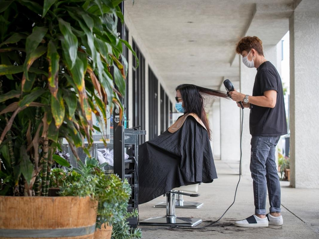 Travis Vu cuts a client's hair in one of two chairs outdoors in front of his TravisVu The Salon in Fountain Valley, as mandated Monday by Gov. Newsom, July 22, 2020.