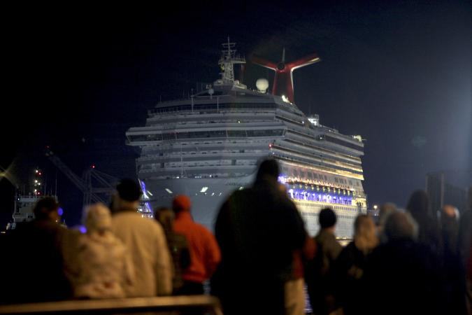 The Carnival Triumph cruise ship is towed towards the dock as spectators watch at the port of Mobile, Alabama, February 14, 2013. The 893-foot (272 meter) vessel, notorious for reports of raw sewage from overflowing toilets, has been without propulsion and running on emergency generator power since Sunday, when an engine room fire left it adrift in the Gulf of Mexico.  REUTERS/ Lyle Ratliff  (UNITED STATES - Tags: SOCIETY HEALTH TRAVEL MARITIME TRANSPORT BUSINESS)