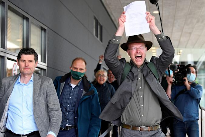 Donald Pols, Director of Milieudefensie (Friends of the Earth), reacts holding a copy of a verdict in a case brought on against Shell by environmentalist and human rights groups, including Greenpeace and Friends of the Earth, who demand the energy firm to cut its reliance on fossil fuels, in The Hague, Netherlands, May 26, 2021. REUTERS/Piroschka van de Wouw