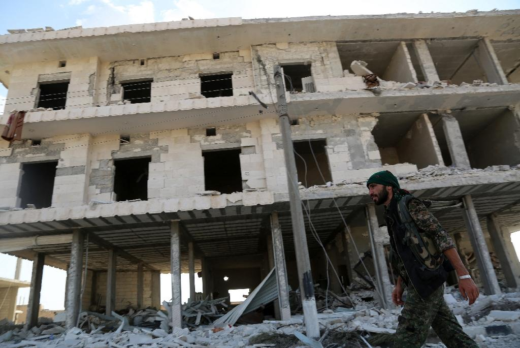 A member of the US-backed Kurdish and Arab fighters walks past destroyed buildings as they advance into the Islamic State jihadist's group bastion of Manbij, in northern Syria, on June 23, 2016 (AFP Photo/Delil Souleiman)