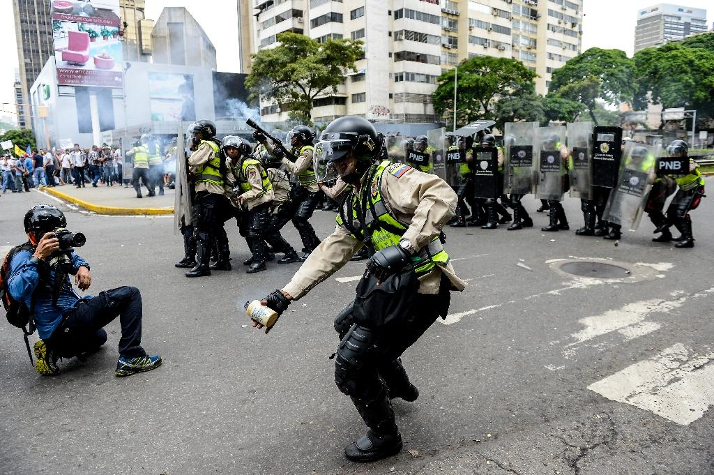 Policemen clash with people protesting against new emergency powers decreed this week by President Nicolas Maduro in Caracas on May 18, 2016 (AFP Photo/Federico Parra)