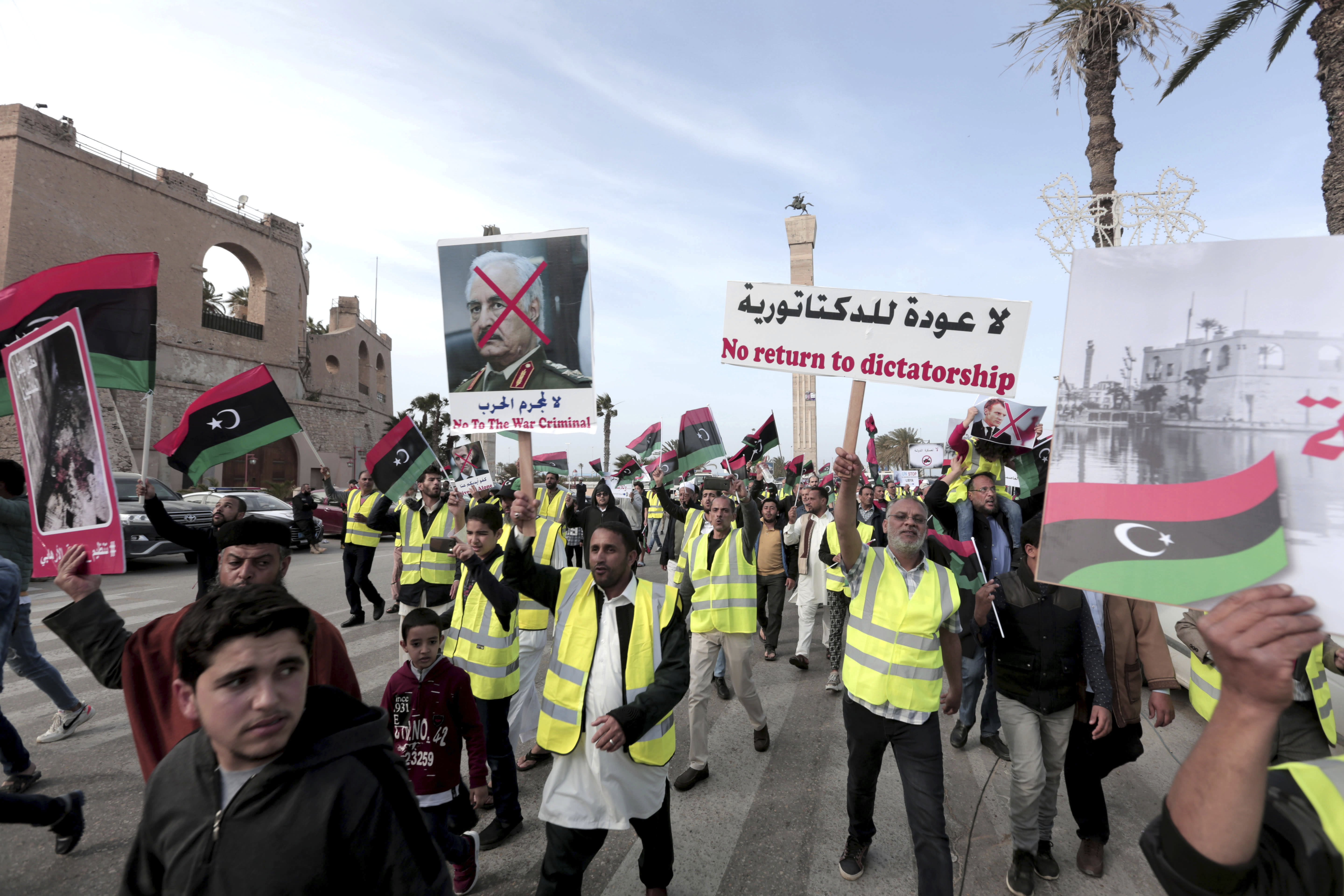 FILE - In this April 19, 2019 file photo, protesters wear yellow vests at a protest as they wave national flags and chant slogans against Libya's Field Marshal Khalifa Hifter, in Tripoli, Libya. Officials in Libya's U.N.-backed administration say they plan to present evidence to Moscow of Russian mercenaries fighting alongside their adversary in their country's war. Libyan officials say up to 800 fighters from the Russian private security contractor Wagner Group have joined the forces of Hifter, the commander of forces battling for months trying to capture Libya's capital, Tripoli. (AP Photo/Hazem Ahmed, File)