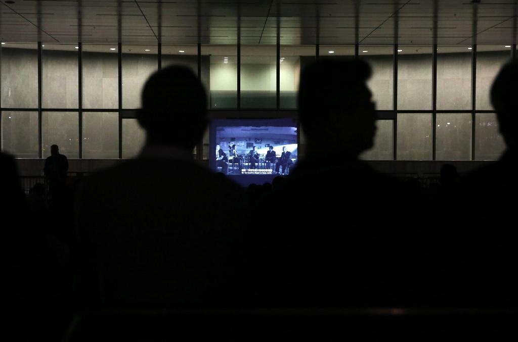 Members of the public watch the dystopian Hong Kong independent film 'Ten Years' on a make-shift screen on April 1, 2016 (AFP Photo/Isaac Lawrence)