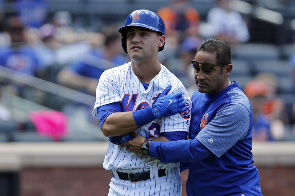 Ray Ramirez helps Michael Conforto off the field after an injury. (AP)
