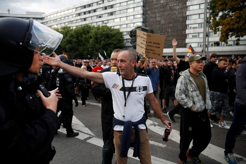 Police watch demonstrators in Chemnitz, eastern Germany, after the stabbing death of a 35-year-old German national sparked violent protests and attacks on foreigners