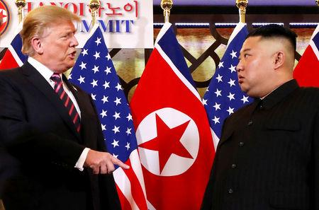 FILE PHOTO: U.S. President Donald Trump speaks to North Korean leader Kim Jong Un after shaking hands before their one-on-one chat during the second U.S.-North Korea summit at the Metropole Hotel in Hanoi, Vietnam February 27, 2019. REUTERS/Leah Millis/File Photo