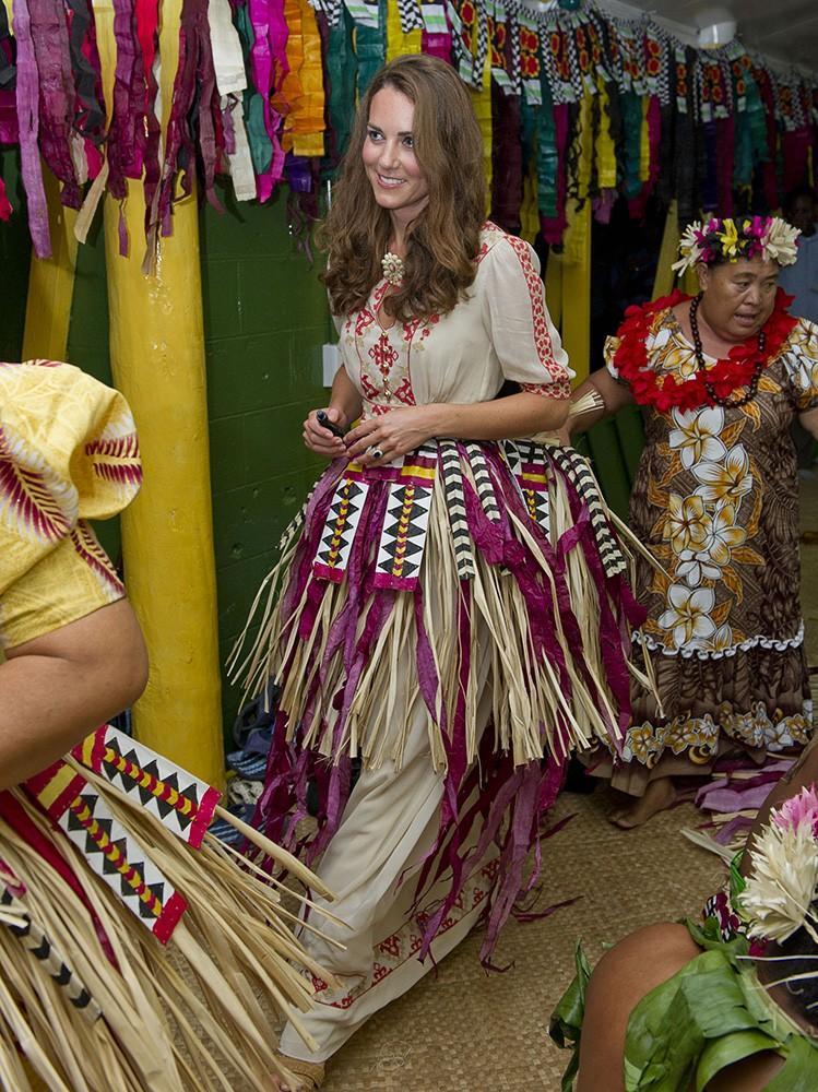 Kate prepared to dance with traditional dancers, in a much cooler grass skirt than we've ever seen.