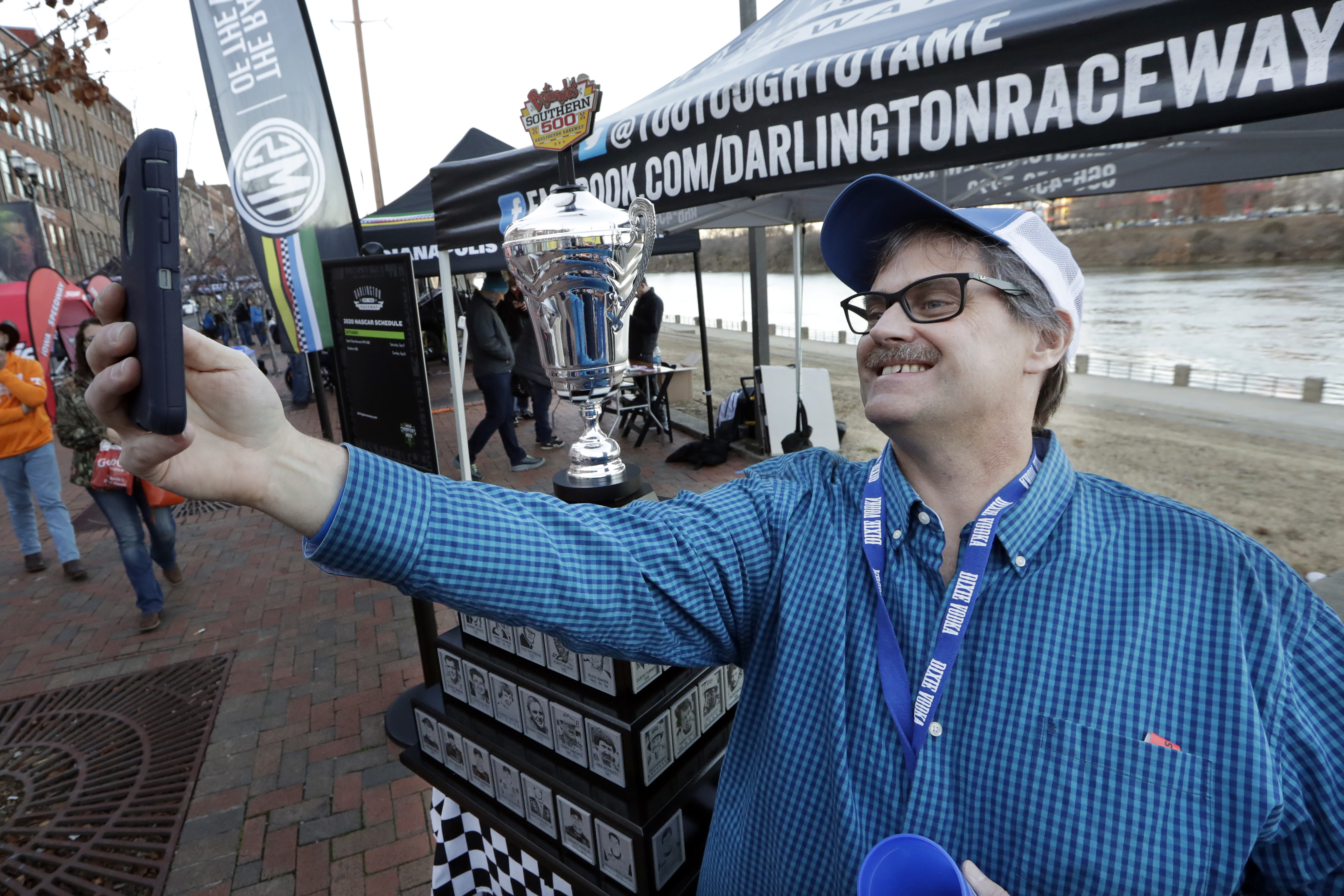 Louis Buckley takes a photo by the Darlington Raceway Southern 500 winner's trophy Wednesday, Dec. 4, 2019, during NASCAR Champion's Week in Nashville, Tenn. (AP Photo/Mark Humphrey)