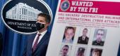 FBI Deputy Director David Bowdich displays a poster showing six wanted Russian military intelligence officers. (AP)