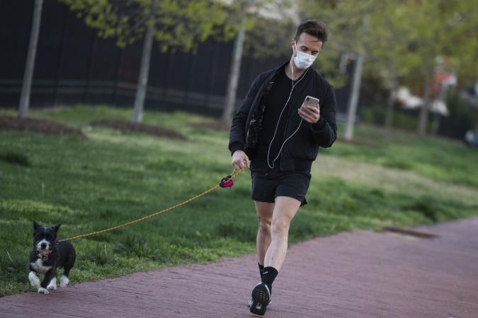 UNITED STATES - APRIL 2: A man walks a dog along New Jersey Avenue, NW, during the coronavirus outbreak on Thursday, April 2, 2020. (Photo By Tom Williams/CQ-Roll Call, Inc via Getty Images)