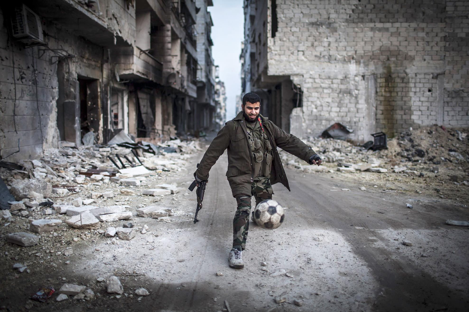 FILE - In this January 2, 2013, file photo, a Syrian rebel plays soccer in the Saif al-Dawlah neighborhood of Aleppo, Syria. For Syria's banned Muslim Brotherhood, the uprising against President Bashar Assad that erupted amid Arab Spring revolts in 2011 provided a long-sought opportunity to stage a comeback after decades spent in exile. (AP Photo/Andoni Lubacki, File)