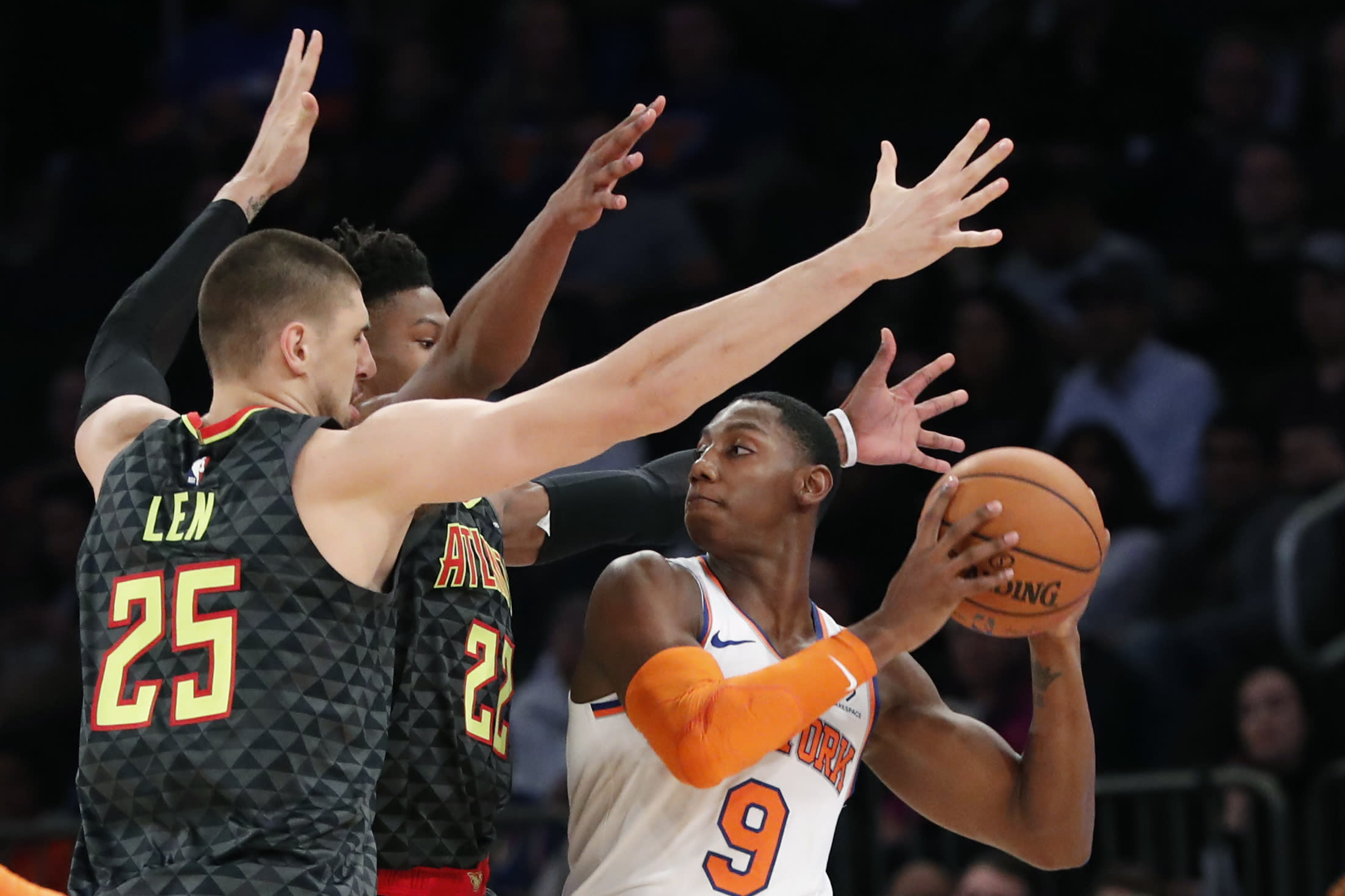 New York Knicks forward RJ Barrett (9) looks to pass with Atlanta Hawks forward Cam Reddish (22) and Hawks center Alex Len (25) defending during the first half of a preseason NBA basketball game in New York, Wednesday, Oct. 16, 2019. (AP Photo/Kathy Willens)