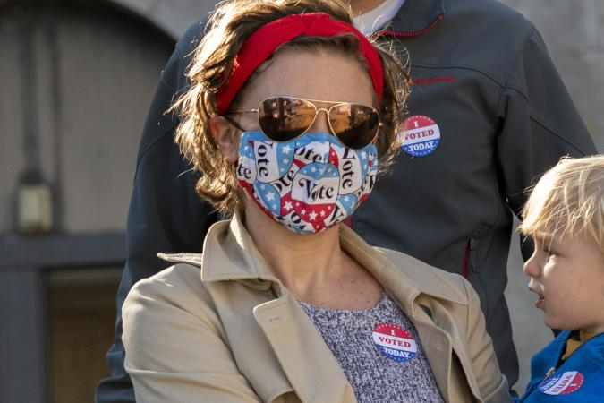 """PHILADELPHIA, PA - OCTOBER 17:  Nya Nelson wears a """"Vote"""" themed mask due to the coronavirus pandemic and an """"I VOTED TODAY"""" sticker while departing with her family after casting their early voting ballots at Roxborough High School on October 17, 2020 in Philadelphia, Pennsylvania.  With the election only a little more than two weeks away, a new form of in-person early voting by using mail ballots, enables millions of voters have already cast their ballots.  President Donald Trump won the battleground state of Pennsylvania by only 44,000 votes in 2016, the first Republican to do so since President George Bush in 1988.  (Photo by Mark Makela/Getty Images)"""