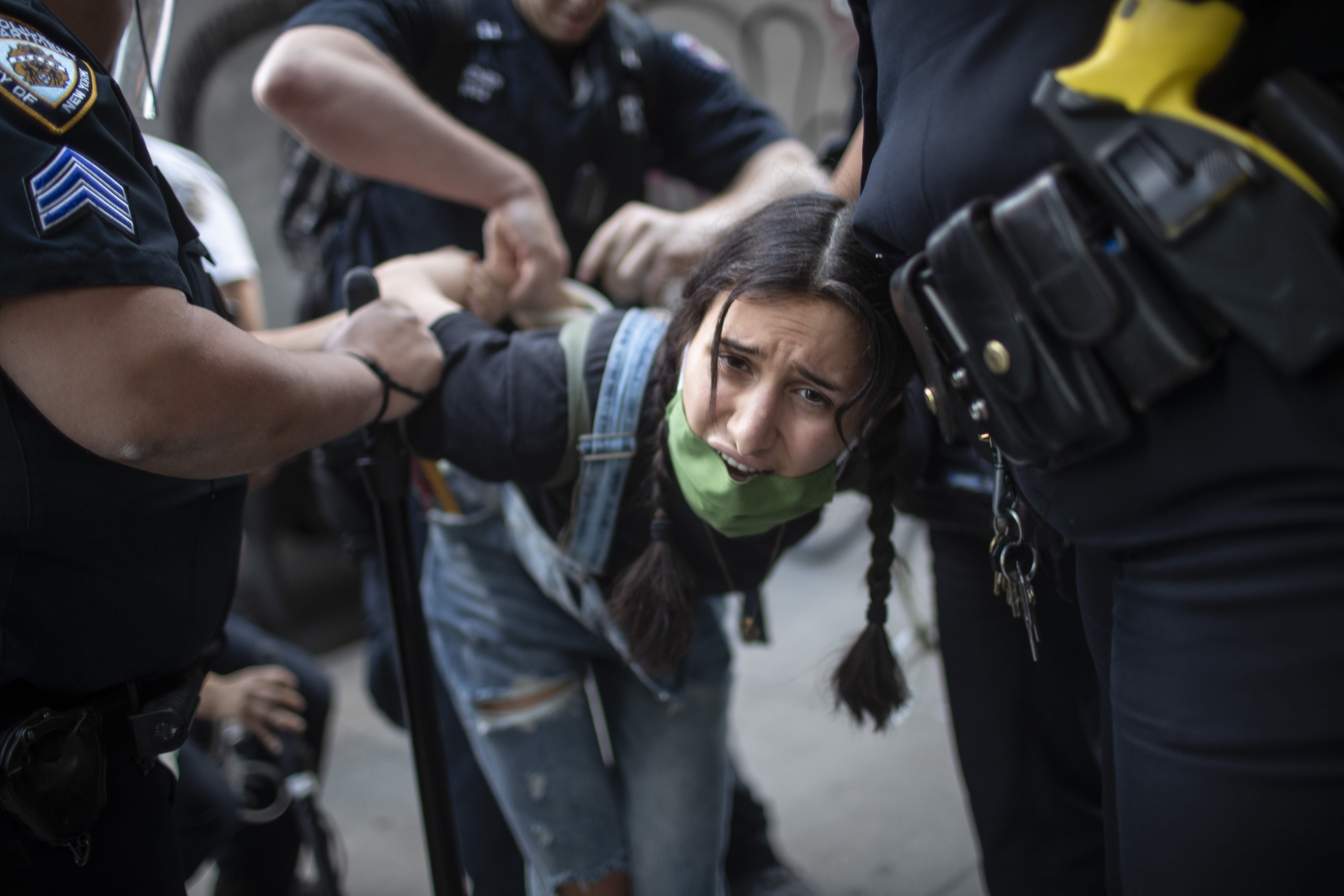 A nude protester is arrested by police during an anti