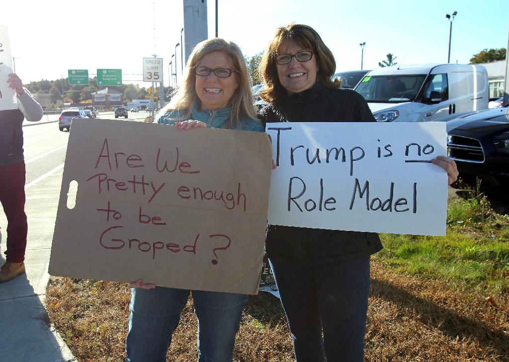 Peggy Cooke (L) and Susan Padgorski, supporters of Democratic presidential candidate Hillary Clinton, protest across the street from a campaign event for Republican presidential candidate Donald Trump on October 15, 2016 in Portsmouth, New Hampshire (AFP Photo/Mary Schwalm)