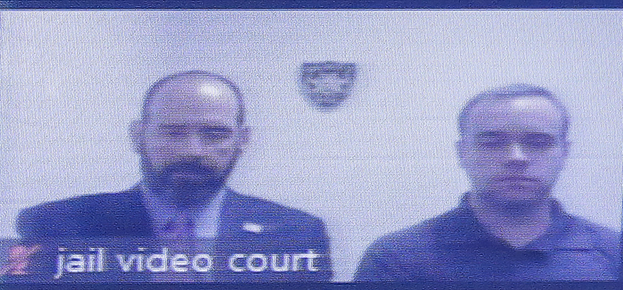 Former Atlanta police Officer Garrett Rolfe, right, appears on a television screen with attorney Lance LoRusso, Tuesday, June 30, 2020, in Atlanta. Rolfe, who fatally shot Rayshard Brooks when Brooks fired a Taser in his direction while running away after a struggle on June 12, can be free on bond while his case is pending. A judge set a bond of $500,000 for Rolfe, who faces charges, including felony murder. (AP Photo/Brynn Anderson, Pool)
