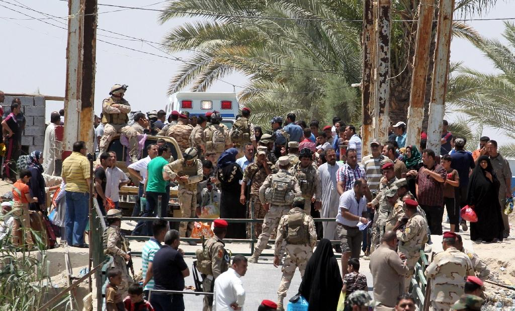 Iraqi security forces stand guard as residents from the city of Ramadi wait to cross Bzeibez bridge, on the southwestern frontier of Baghdad, on May 16, 2015 after fleeing Islamic State militants (AFP Photo/Sabah Arar)