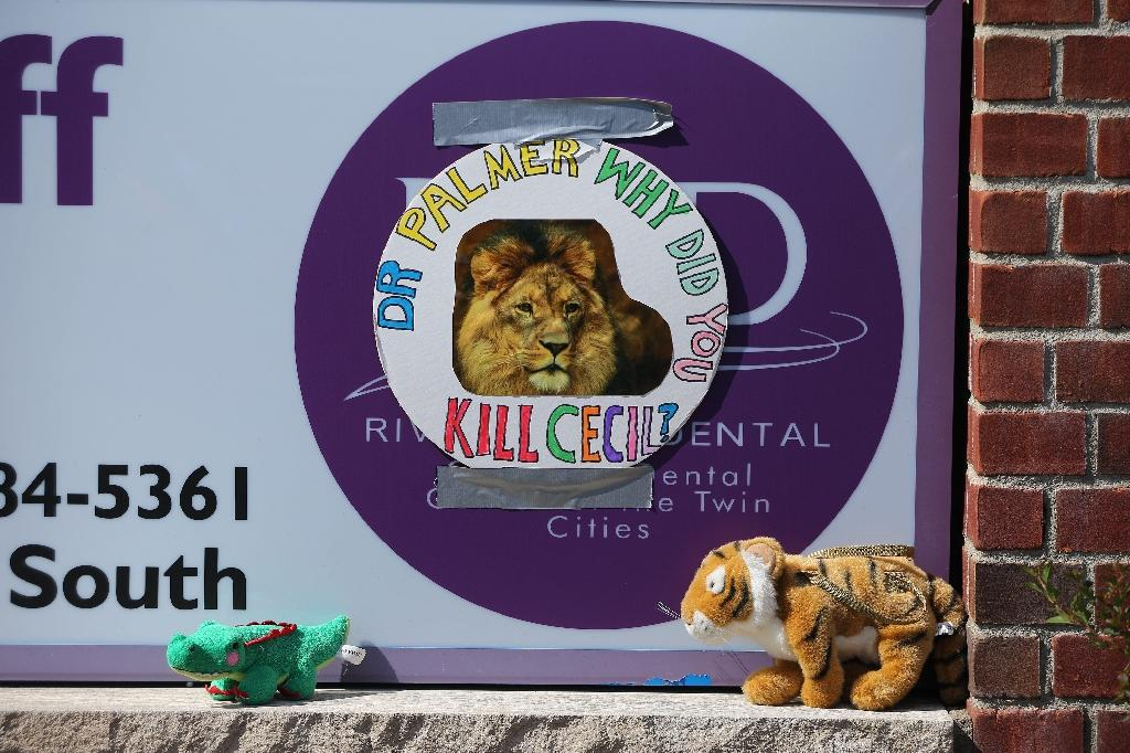 Protesters place stuffed animals on the sign of Dr. Walter Palmer's River Bluff Dental Clinic to call attention to the alleged poaching of Cecil the lion on July 29, 2015 in Bloomington, Minnesota (AFP Photo/Adam Bettcher)