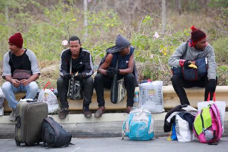 Venezuelan migrants wait to pass the frontier near the binational border service center of Peru at the border with Ecuador, in Tumbes, Peru August 24, 2018. REUTERS/Douglas Juarez
