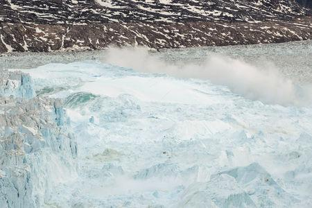 FILE PHOTO: Ocean water is pushed up by the bottom of a pinnacle iceberg as it falls back during a large calving event at the Helheim glacier near Tasiilaq, Greenland
