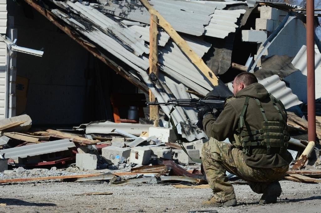 A soldier of the self-proclaimed Donetsk People's Republic secures a street in front of a recently damaged building in Shyrokyne, near Mariupol, on March 20, 2015 (AFP Photo/John MacDougall)