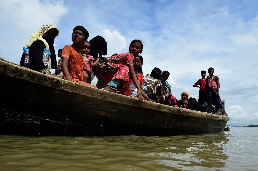 Rohingya Muslim refugees from Myanmar disembark from a boat on the Bangladeshi side of Naf river on September 12, 2017
