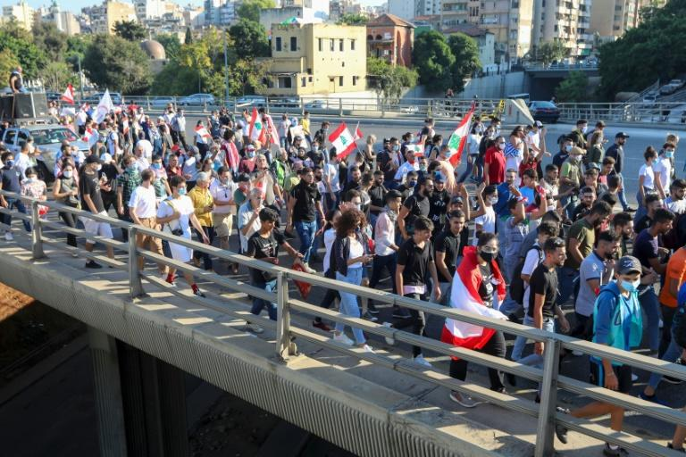 Lebanese demonstrators wave the national flag during a demonstration, marking the first anniversary of a non-sectarian protest movement, in the capital Beirut on Saturday