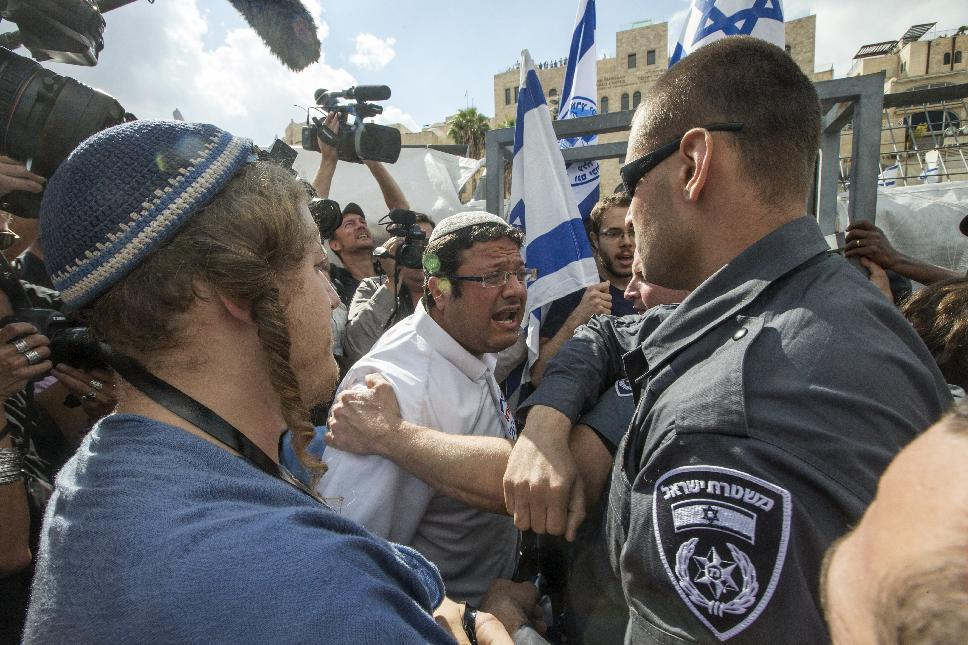 Israeli policemen scuffle with right-wing Israelis who were trying to jump a barrier to cross into the al-Aqsa mosque compound in the old city of Jerusalem, on October 30, 2014 after Israeli authorities temporarily closed the compound (AFP Photo/Jack Guez)