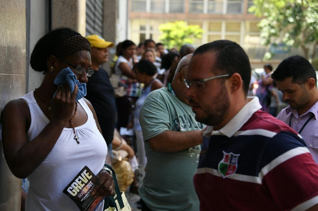 Public servants of Rio de Janeiro state queue outside their union building to receive food and other supplies donated by volunteers and colleagues (AFP Photo/VANDERLEI ALMEIDA)