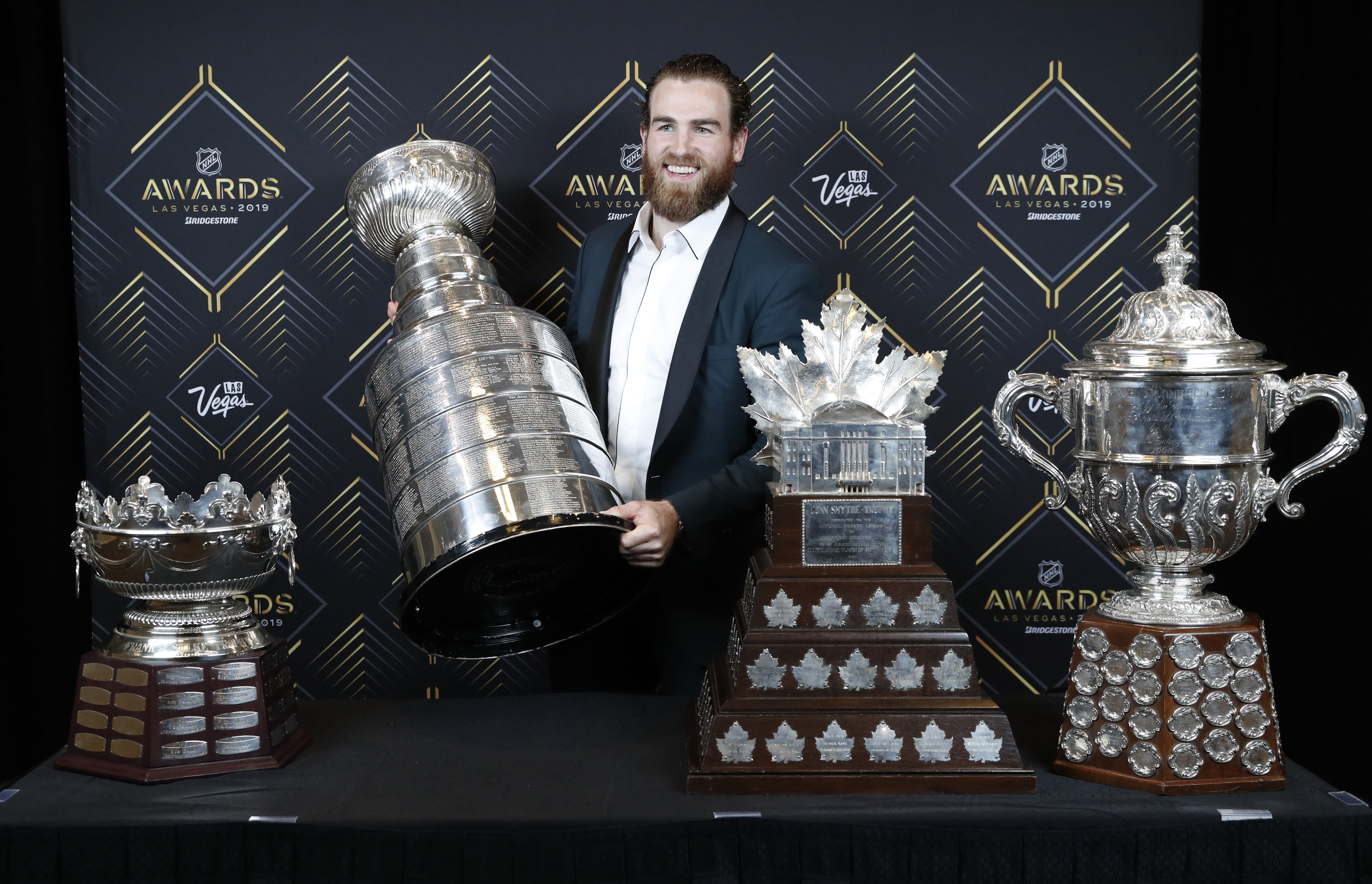 FILE - In this June 19, 2019, file photo, St. Louis Blues' Ryan O'Reilly poses with, from left, the Frank J. Selke Trophy, for top defensive forward; the Stanley Cup; the Conn Smythe Trophy, for MVP during the playoffs; and the Clarence S. Campbell Bowl, for the Western Conference playoff champions, at the NHL Awards in Las Vegas. Ryan O'Reilly stockpiled quite the hardware to show off at his Stanley Cup day. On display next to the Cup he helped the St. Louis Blues win were the Conn Smythe Trophy as playoff MVP and the Selke Trophy as the NHL's best defensive forward. Any player would gladly celebrate with those shiny centerpieces, though O'Reilly at 28 and on his third team is only now showing he's this kind of elite player.(AP Photo/John Locher, File)