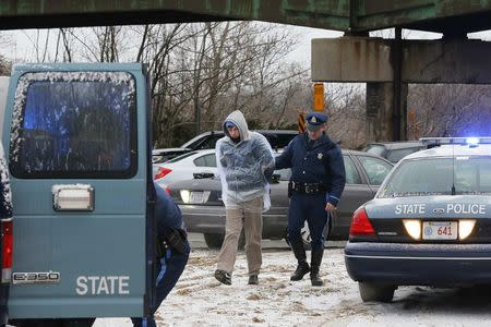 Police detain a protester who was part of a group who blocked Interstate 93 southbound during the morning rush hour in Somerville, Massachusetts January 15, 2015. REUTERS/Brian Snyder
