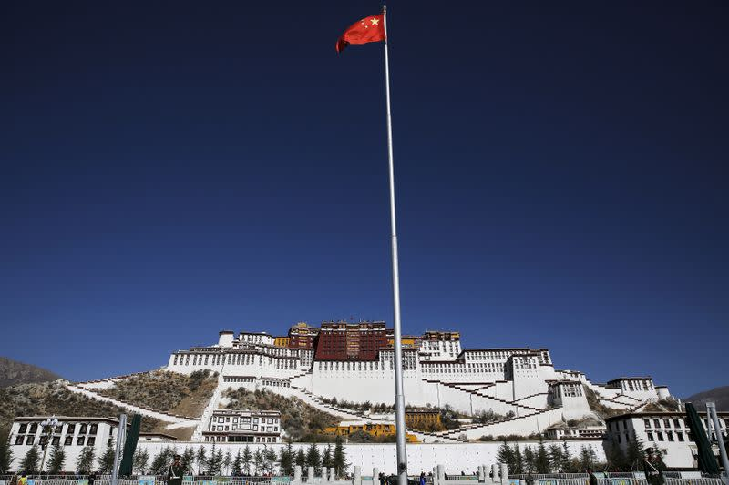 FILE PHOTO: A Chinese flag flutters on a pole in front of the Potala Palace in Lhasa, Tibet Autonomous Region