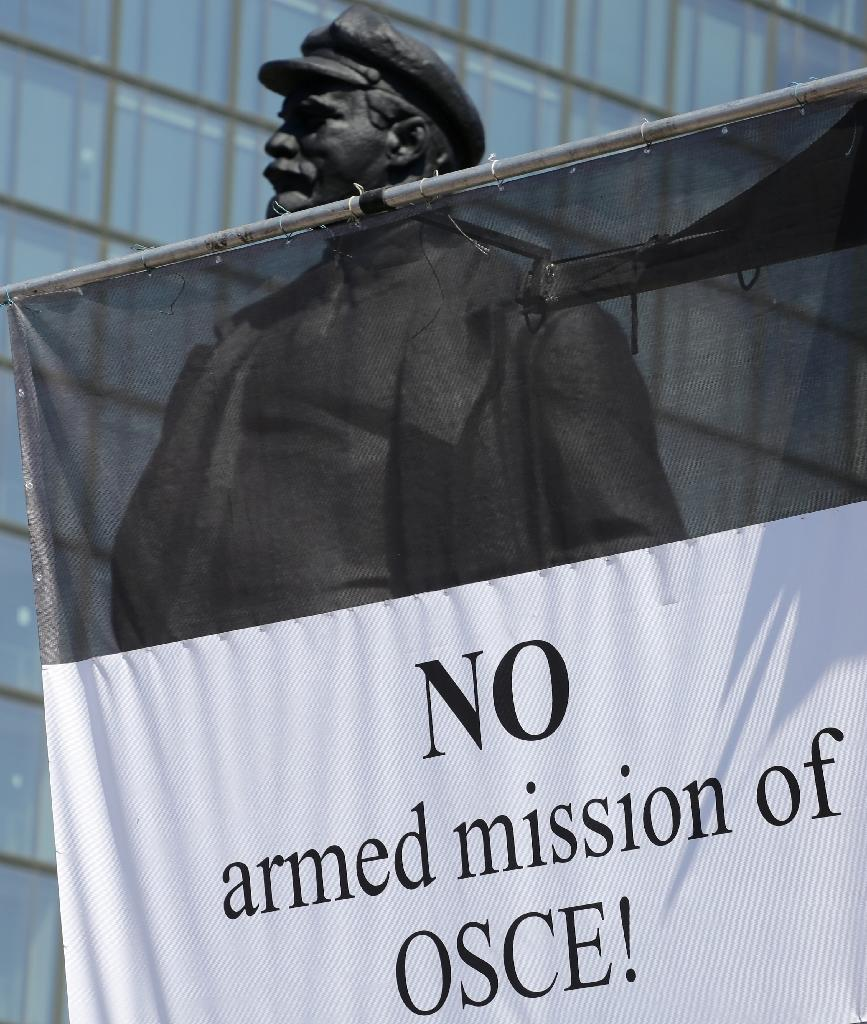 "A banner reading ""No armed mission of OSCE!"" hanging next to a statue of former head of the Russian Republic Vladimir Lenin during a rally against the presence of Organization for Security and Cooperation (OSCE) monitors in Donetsk on June 10, 2016 (AFP Photo/Aleksey Filippov)"