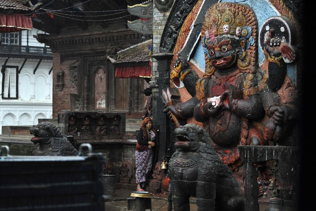 A Nepalese resident (C) perfoms a 'puja' morning prayer at a temple in the earthquake-damaged Durbar Square at dawn in Kathmandu on April 30, 2015 (AFP Photo/Prakash Mathema)