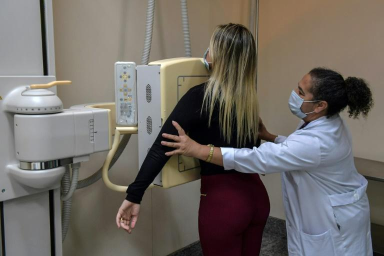 A medical worker puts a patient in position for a chest x-ray at the University of Sao Paulo Clinical Hospital (AFP Photo/NELSON ALMEIDA)