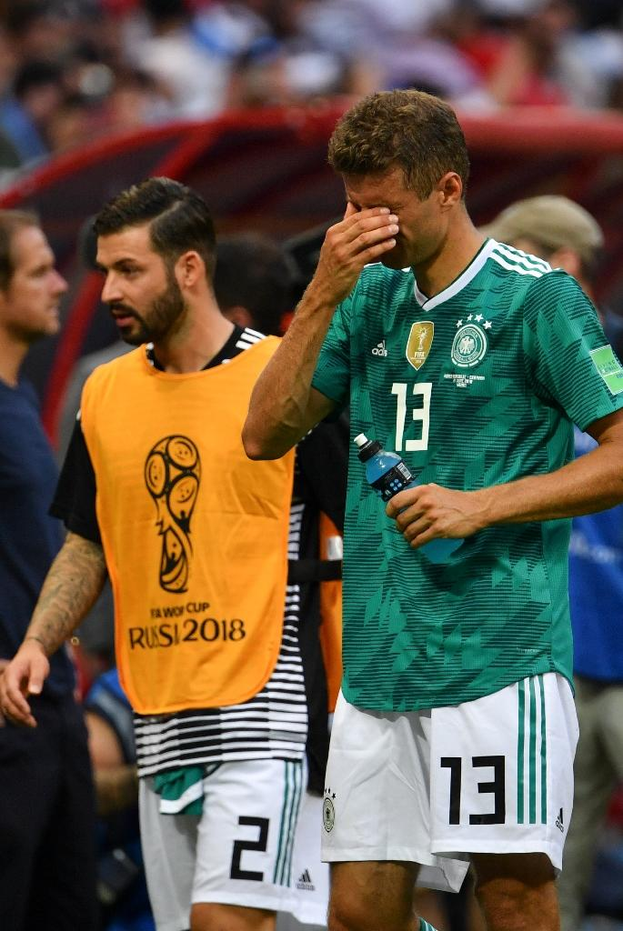 Germany's forward Thomas Mueller (R) says the squad is 'shocked and stunned' by the early World Cup exit. (AFP Photo/SAEED KHAN)