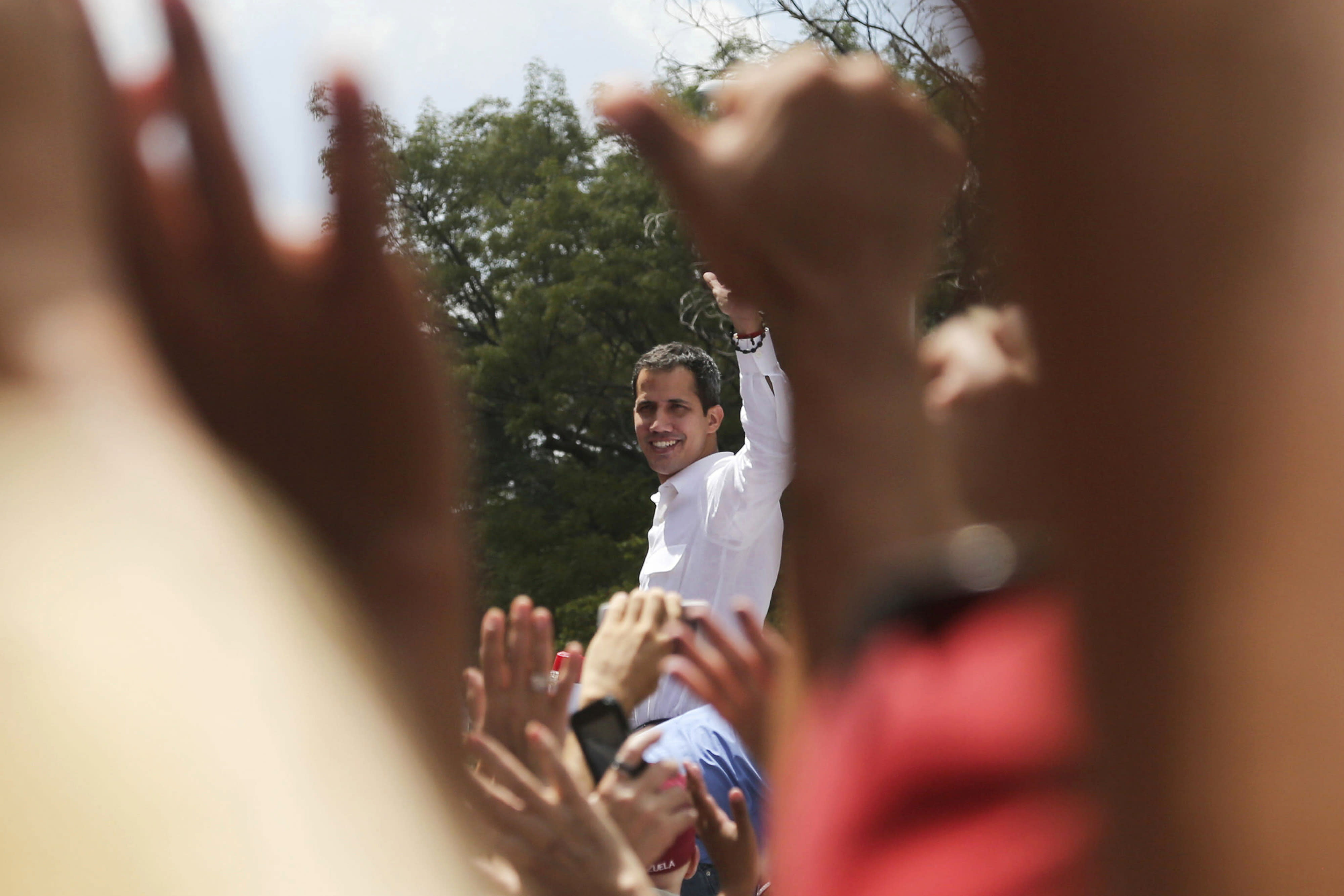 The leader of Venezuela's National Assembly Juan Guaido who declared himself the country's interim president, greets supporter upon his arrival to a rally against the government of President Nicolas Maduro in Caracas, Venezuela, Saturday, March 9, 2019. (AP Photo/Fernando Llano)