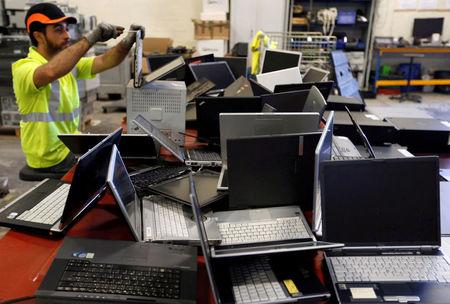 FILE PHOTO: A worker at the Ecomicro recycling company dismantles computers in Saint-Loubes near Bordeaux, France October 16, 2017. REUTERS/Regis Duvignau/File Photo