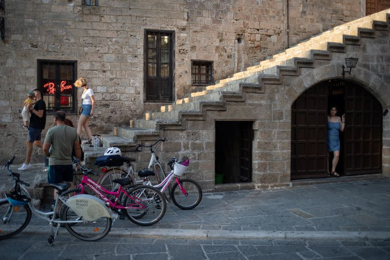 A shop owner looks through a door as people visit the Old Town of Rhodes, following the coronavirus disease (COVID-19) outbreak, on the island of Rhodes